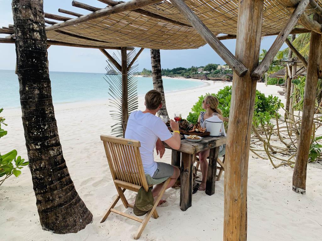 Paar beim Lunch am weißen Sandstrand